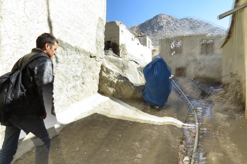 Going up the hill. The water pipe can be seen in a gulley. Zuhair's mother walks in front of Zek.