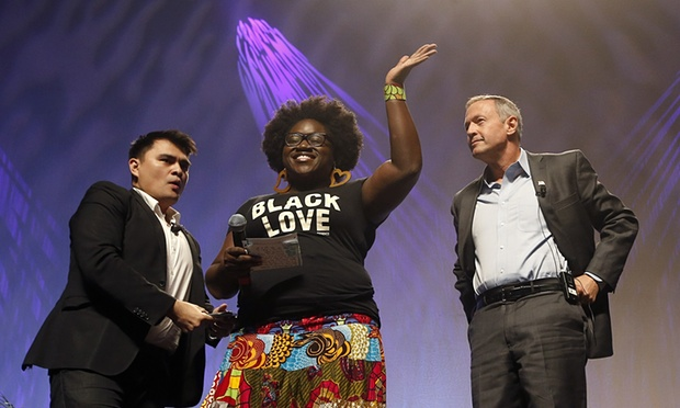 Tia Oso of the National Coordinator for Black Immigration Network joins moderator Jose Antonio Vargas and Democratic candidate Martin O'Malley onstage. (Photograph: Ross D. Franklin/AP)
