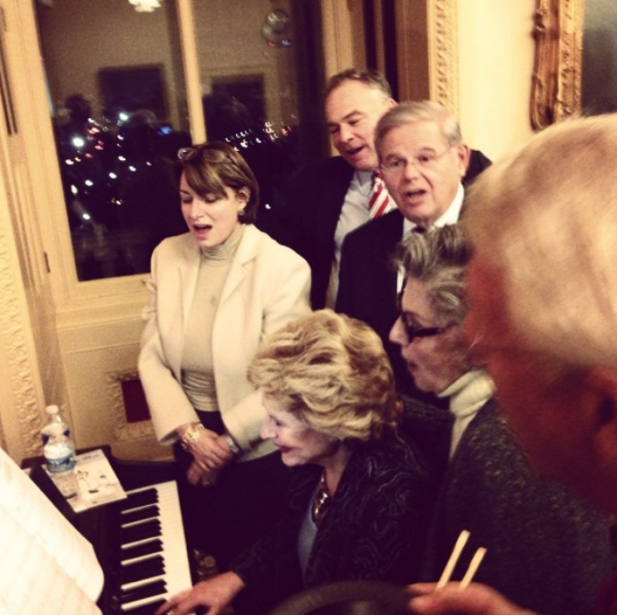 "Sen. Cory Booker wrote of the impromptu session: ""Pictured here are Debbie Stabenow (an impressive piano player), my senior Senator who has a great voice Bob Menendez, Barbara Boxer, Roger Wicker, Tim Kaine and Amy Klobuchar. This was truly a memorable experience. #CRomnibusCarols"""