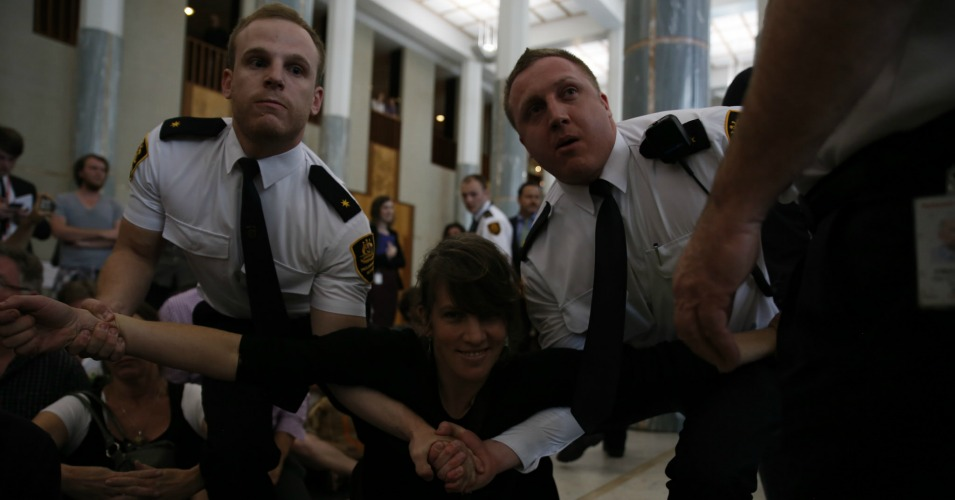 A climate protesters is dragged away by security officers.  (Photo:350 .org/flickr/cc)