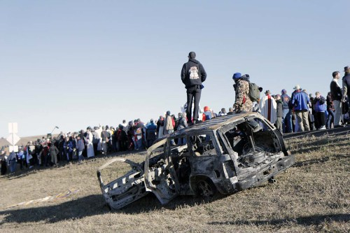 A man stands on a burnt-out SUV as interfaith witnesses share testimony and commit to carrying with them home the message from Standing Rock.