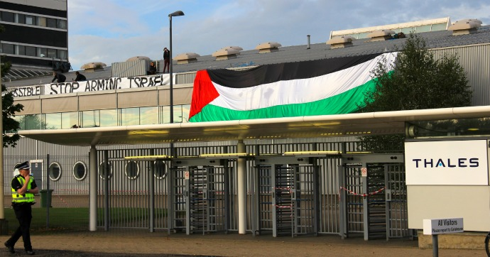 Activists occupying the roof drape banner over the side of the factory. (Photo Couresty of Glasgow Palestine Action)