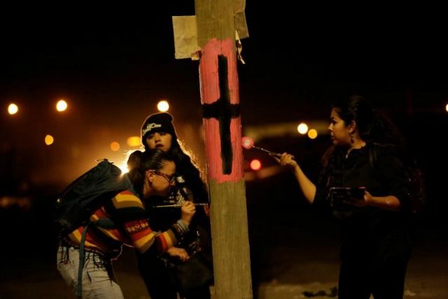 Women paint a black cross on a lamp post to commemorate missing and murdered women in Juarez, Mexico. (Photo: Reuters)