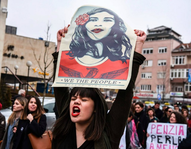 A demonstrator hods up a Shepard Fairey sign in Kosovo. (Photo: Getty)