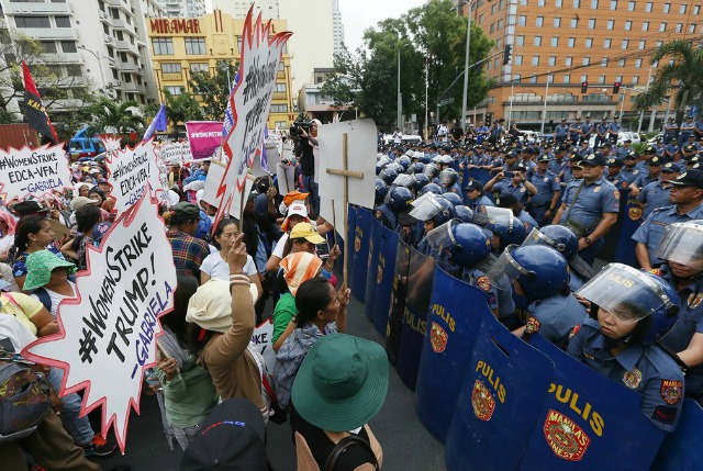 Protesters meet a line of riot police as they attempt to march to the U.S. embassy in Manila. (Photo: AP)
