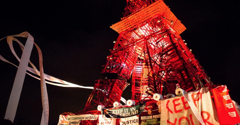 Civil Society groups attached signs to a mock Eiffel tower following Wednesday's mass sit-in. (Photo: Emma Cassidy/Survival Media Agency)