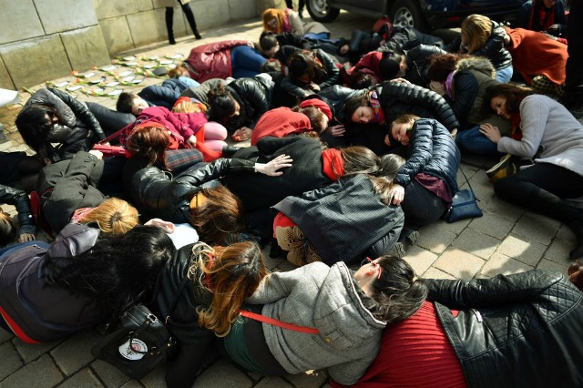 Romanian women lie on the floor of a police station to protest a lack of protection for abused women. (Photo: Getty)
