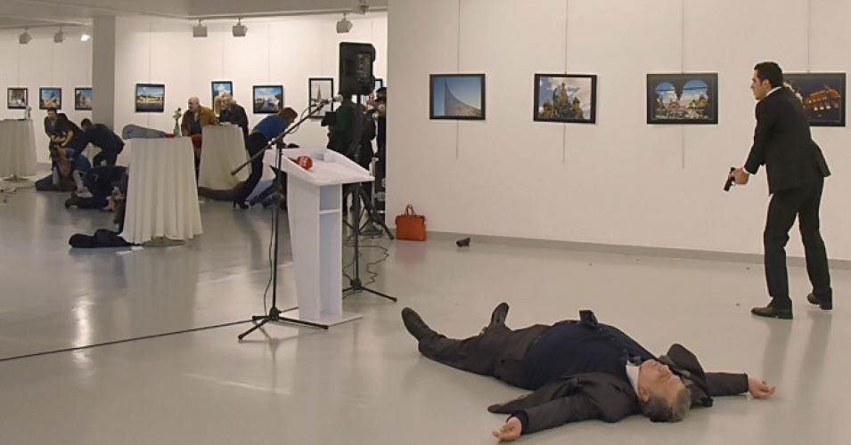 A man, right, reported by The Associated Press to be the gunman, after the shooting of the Russian ambassador Andrei Karlov, on the floor, on Monday at a gallery in Ankara, the capital of Turkey. (Credit: Yavuz Alatan/Agence France-Presse — Getty Images)