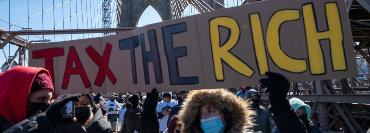 """Activists march with a """"Tax the Rich"""" sign"""