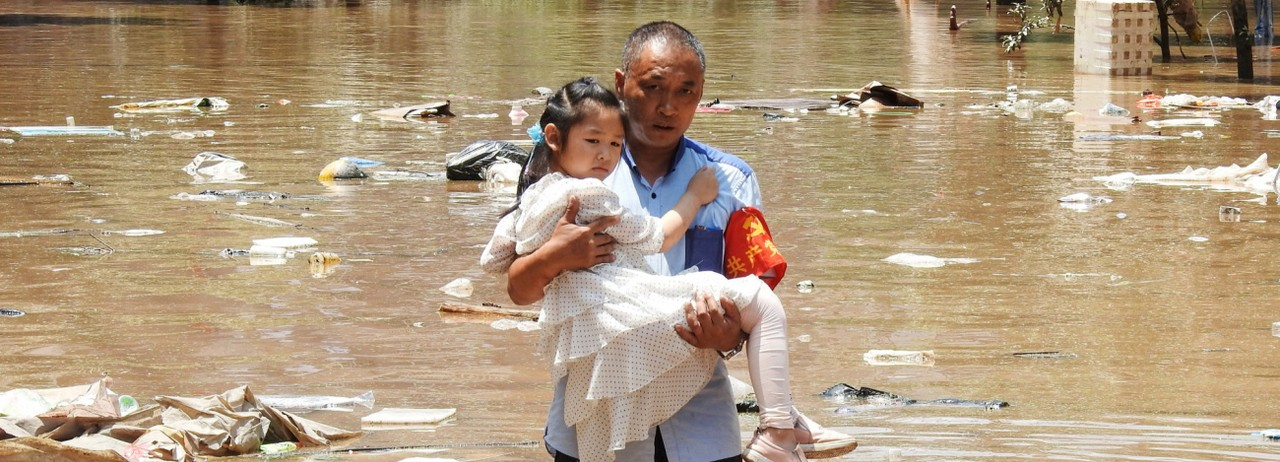 A girl is carried to safety after flooding in southern China