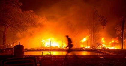 A firefighter walks near a pool as a neighboring home burns in the Napa wine region in California. (Photo: Josh Edelson/AFP/Getty Images)