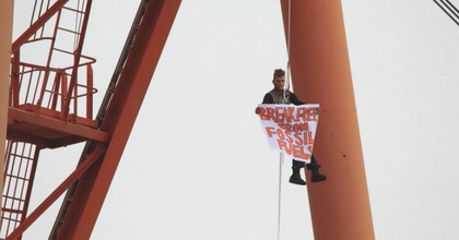 An activist hangs from a coal loader in Newcastle Harbour, Australia. (Photo: 350 Australia)