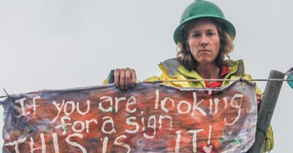 Climate activist Abby Brockway sits atop a tripod blocking a BNSF oil train in Everett, Washington in September 2014. (Photo: the Delta 5)