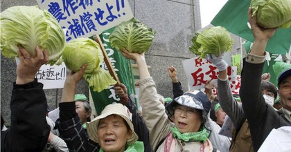 Farmers hold up cabbages during a 2011 protest in front of the Tokyo Electric Power Co. (TEPCO) headquarters in Tokyo. (Photo: AP)