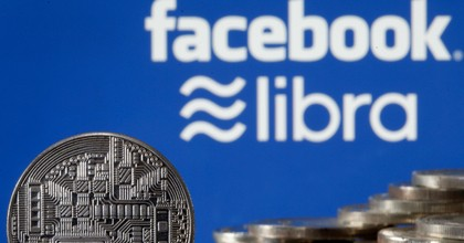 In this photo illustration, a visual representation of a digital cryptocurrency coin sits on display in front of Libra and Facebook logos on June 24, 2019 in Paris, France. (Photo: Chesnot/Getty Images)