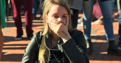 """A young woman covers her mouth in protest across from Senator Susan Collins office in Portland, Maine while Collins announced her decison to vote """"yes"""" on Brett Kavanaugh. (Photo: Jenna McGuire/Common Dreams)"""