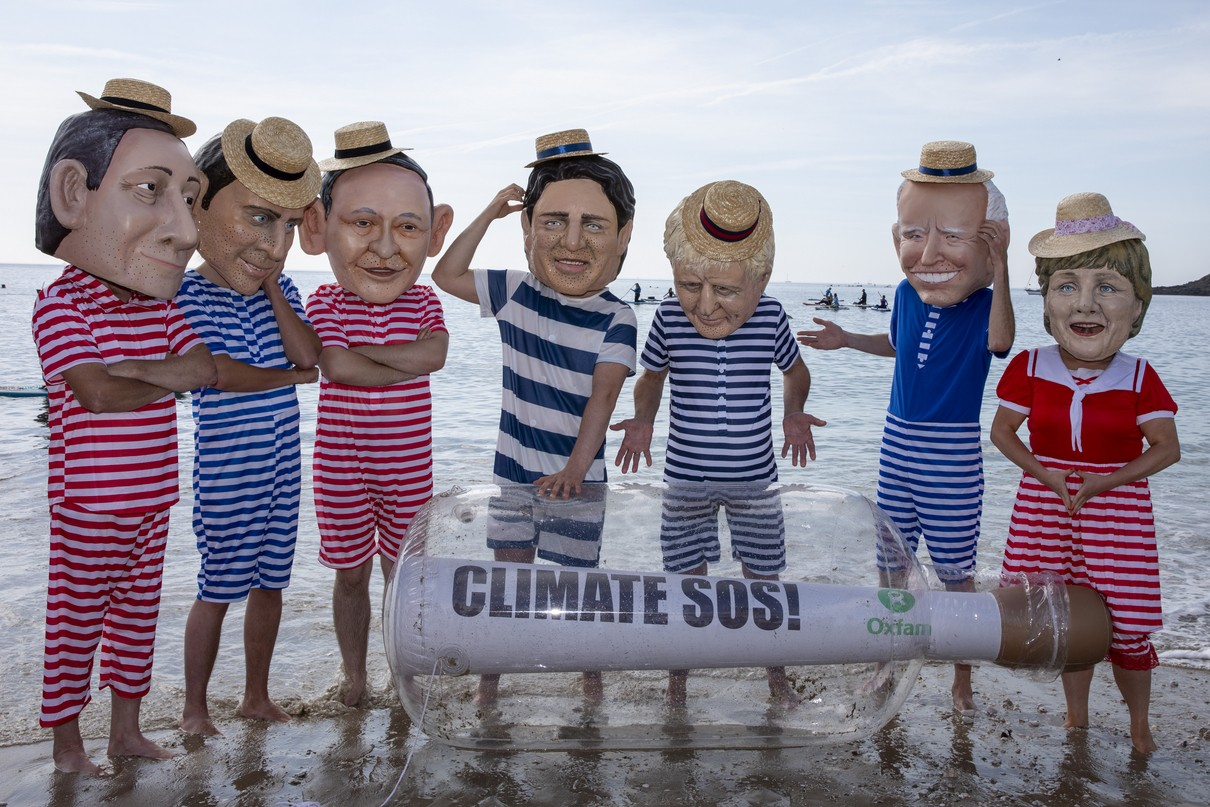A giant message in a bottle has washed up on the beach from countries ravaged by climate change, but the G7 leaders are too busy relaxing in their swimming costumes in deck chairs to notice, Oxfam campaigners pose as G7 leaders on a beach on the 12th of June 2021 near Falmouth, Cornwall, United Kingdom.