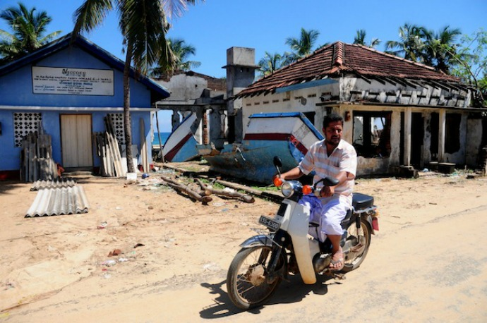 A man rides his bike by houses destroyed by the tsunami in the Karathivu area in Kalmunai. (Photo: Amantha Perera/IPS)