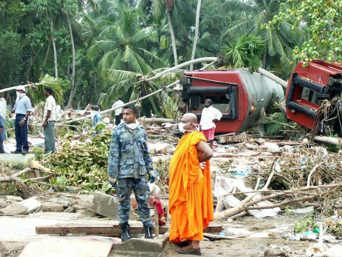 A Buddhist monk stands with a military officer in front of a train that was washed away by the waves in the southern village of Peraliya, killing over 1,000 people. (Photo: Amantha Perera/IPS)