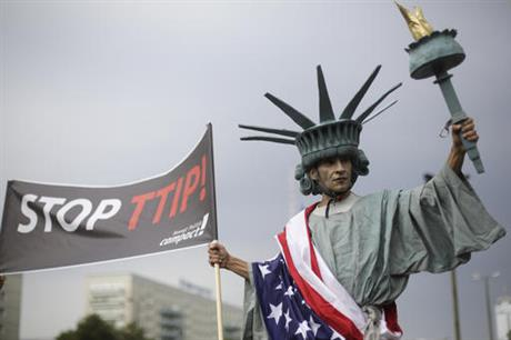 A man dressed like the Statue of Liberty attends a demonstration against the planned Transatlantic Trade and Investment Partnership, TTIP, and the Comprehensive Economic and Trade Agreement, CETA in Berlin, Saturday, Sept. 17, 2016. Thousands of people are rallying in cities across Germany to protest against planned European Union trade deals with the United States and Canada. (AP Photo/Markus Schreiber)