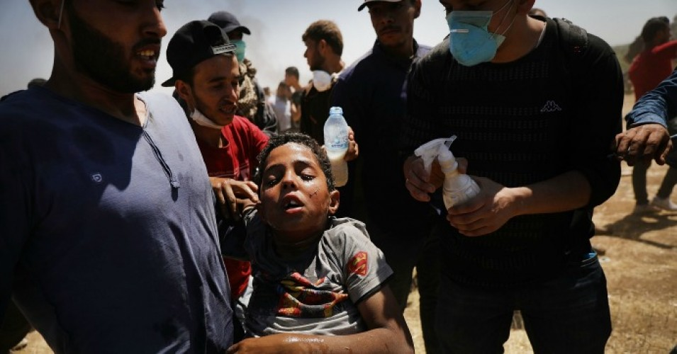 A child overcome by tear gas is rushed to medics at the border fence with Israel as mass demonstrations continue on May 14, 2018 in Gaza City, Gaza. Israeli soldiers killed at least 41 Palestinians and wounded over a thousand as the demonstrations coincided with the controversial opening of the U.S. Embassy in Jerusalem. This marks the deadliest day of violence in Gaza since 2014. (Photo: Spencer Platt/Getty Images)