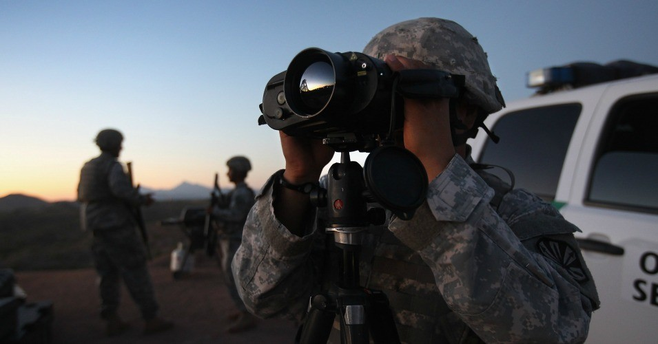 U.S. Army National Guardsman Sgt. Oscar Escobar scans the U.S.-Mexico border at dusk on June 22, 2011 in Nogales, Arizona. (Photo by John Moore/Getty Images)