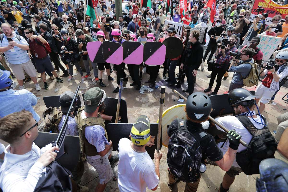 Battle lines form between white nationalists, neo-Nazis and members of the 'alt-right' and anti-fascist counter-protesters at the entrance to Lee Park during the 'Unite the Right' rally August 12, 2017 in Charlottesville, Virginia. After clashes with anti-fascist protesters and police the rally was declared an unlawful gathering and people were forced out of Lee Park, where a statue of Confederate General Robert E. Lee is slated to be removed. (Photo by Chip Somodevilla/Getty Images)