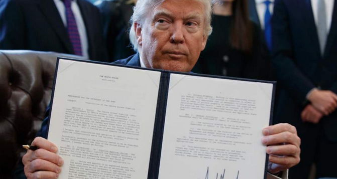 President Trump showed off his signature on an executive order designed to advance construction on the Dakota Access pipeline during an Oval Office signing ceremony last year. Friday's signing of a controversial law that reauthorizes warrantless surveillance happened without cameras.  (Photo: Evan Vucci/AP)