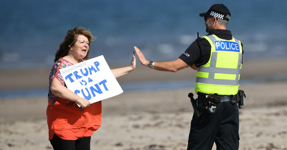 Scottish stand-up comedian Janey Godley gives a high-five to a police officer as she holds a sign in protest stating 'Trump is a runt' on the beach outside near Trump Turnberry Luxury Collection Resort during the U.S. President's visit to the United Kingdom on July 14, 2018 in Turnberry, Scotland. The President of the United States and First Lady, Melania Trump on their first official visit to the UK after yesterday's meetings with the Prime Minister and the Queen is in Scotland for private weekend stay at his Turnberry. (Photo: Leon Neal/Getty Images)