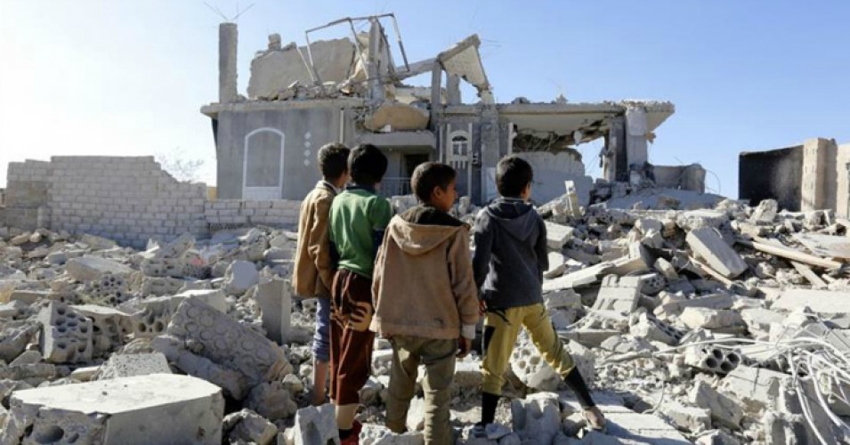Yemeni children stand in front of a building destroyed by airstrikes. (Photo: Yahya Arhab/EPA)