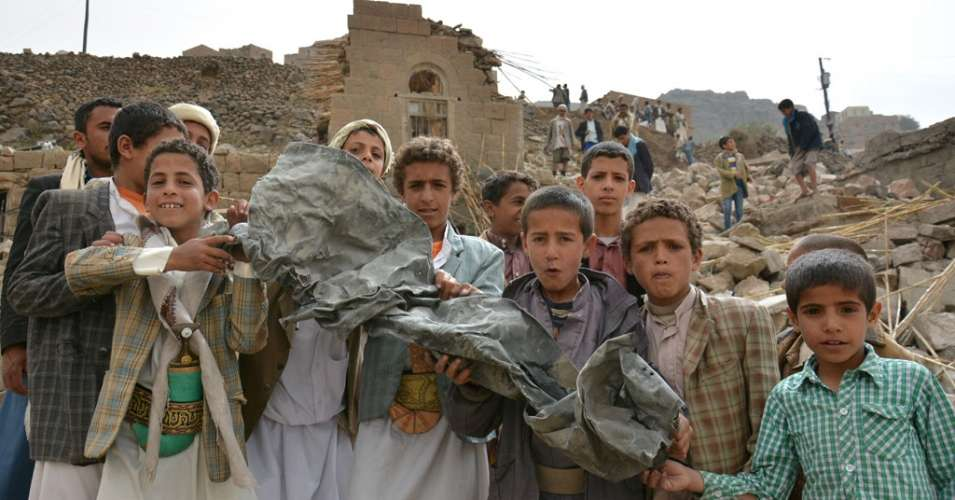 Boys hold a large piece of twisted metal near homes that were destroyed in an air strike in Okash Village, near Sana'a, the capital of Yemen in 2017. (Photo: UNICEF/Mohammed Hamoud)