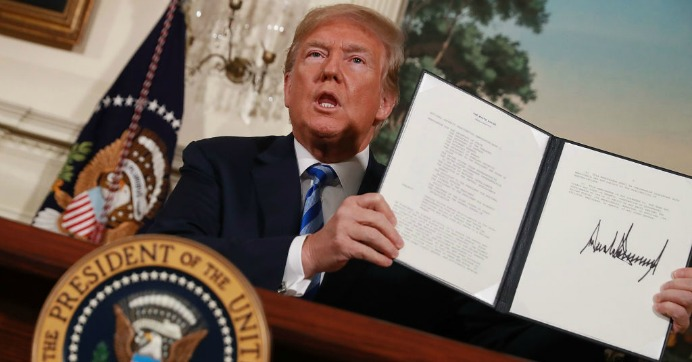 President Donald Trump holds up a memorandum that re-instates sanctions on Iran after he announced his decision to withdraw the United States from the 2015 Iran nuclear deal in the Diplomatic Room at the White House May 8, 2018 in Washington, D.C. (Photo: Chip Somodevilla/Getty Images)