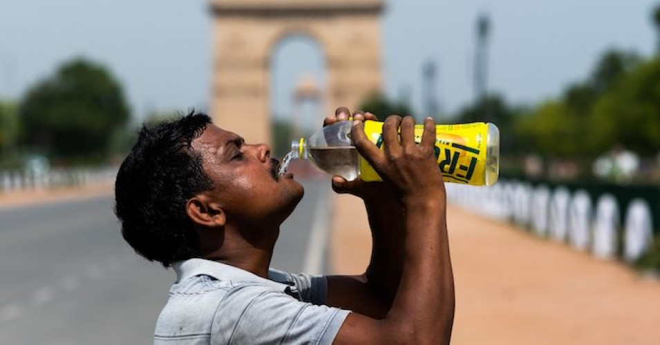 A worker quenches his thirst with water from a bottle taking a break from cleaning weeds from a park near India Gate amid rising temperatures in New Delhi on May 27, 2020. India is wilting under a heatwave, with the temperature in places reaching 50 degrees Celsius (122 degrees Fahrenheit) and the capital enduring its hottest May day in nearly two decades. (Photo: Jewel Samad/AFP via Getty Images)