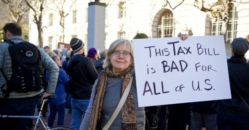 "A woman holds a sign at a protest of the ""Trump tax scam"" on Dec.4, 2017. (Photo: CDEL Family/Flickr/cc)"