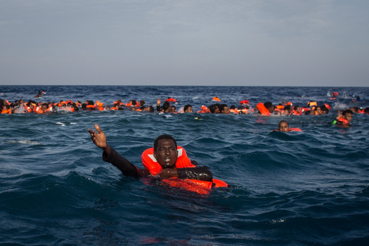 Refugees are seen swimming and yelling for assistance after a wooden boat bound for Italy carrying more than 500 people capsized on May 24, 2017 off Lampedusa, Italy.  (Photo: Chris McGrath/Getty Images)