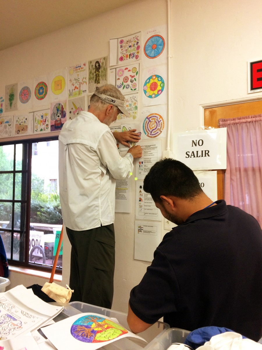 A guest and a local volunteer work to curate a wall of children's drawings in the clothing room. (Photo: Rose Lambert-Sluder)