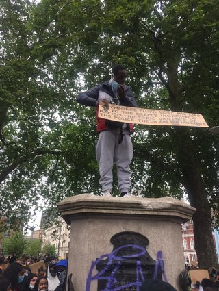 A protester standing on the empty plinth, just vacated by Colston's statue. (Photo: Helen Wilson-Roe)