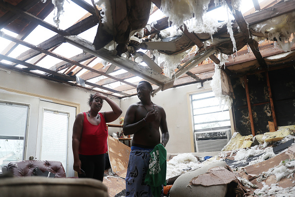 Latasha Myles and Howard Anderson stand in their living room where they were sitting when the roof blew off around 2:30am as Hurricane Laura passed through the area on August 27, 2020 in Lake Charles, Louisiana . The hurricane hit with powerful winds causing extensive damage to the city. (Photo: Joe Raedle/Getty Images)
